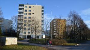 Två barn går framför två höghus