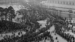 Ett svartvitt gammalt fotografi där man uppifrån ser en gata fylld av ett långt tåg av folk.