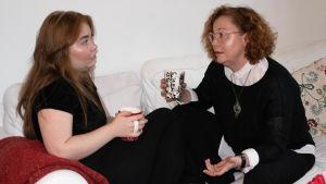 Vivi och Heidi sitter i soffan med kaffekoppar i handen och diskuterar.