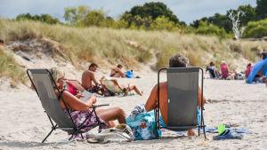 Ett medelålders par solar i varsin solstol på en strand. I bakgrunden flera solbadare.