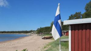 En solig sommardag vid Gunnarsstrand i Hangö. Sandstrand, knallblå himmel, miniflagga (Finlands) vid en fiskebod. Flera fiskebodar och båtar längs stranden.