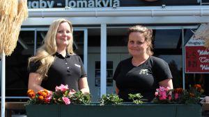 Två leende kvinnor står framför en blomplantering på en terrass.