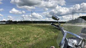 en motorcykel invid en åker och bilväg