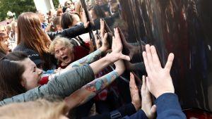 Kvinnor försöker stoppa ett polisfordon under en demonstration i Minsk i Belarus.