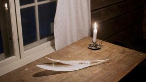 Kaksi sulkaa ja palava kynttilä pöydällä