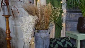 Två vaser med olika sorters torkat gräs.