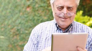 Glad äldre man tittar på sin pekplatta.
