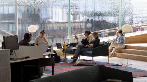 Studerande sitter i soffor och på trappsteg och studerar vid Helsingfors stadsbibliotek Odes stora fönster.