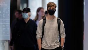 En ung man kommer gående mot kameran med munnen och näsan täckt av ett munskydd.