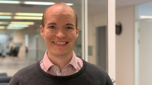 En leende man med rosa skjorta står i ett kontorslandskap.
