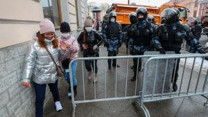 Personer promenerar runt vägstängsel på en trottoar i Moskva.