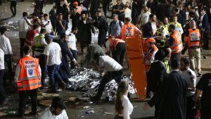 Räddningsarbetare och pilgrimer samlade runt dödsoffer vid Mount Meron, natten till fredagen.