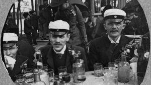 En svartvit gammal bild på tre män som i studentmössor som sitter vid ett bord utomhus med många urdruckna glas framför sig.