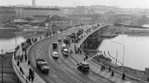 Ett foto av Hagnäs bro strax efter dess invigning 1961. Människor och bilar passerar åt båda hållen.