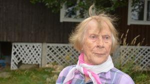 Äldre kvinna med scarf runt halsen.