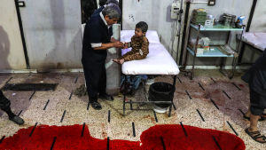 En sjukskötare plåstrar om ett barn medan andra tvättar bort blod från golvet