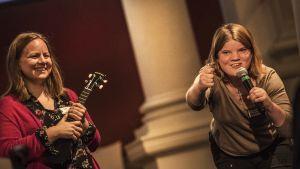 En kvinna talar i mic, en annan ler med ett stränginstrument i handen på scen