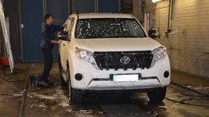 Man tvättar bil.