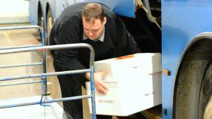 Busschaufför Thomas Friberg lastar av paket från sin buss.