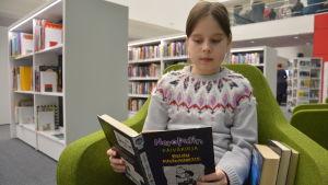 Flicka läser en bok.
