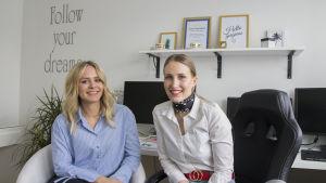 """Två kvinnor sitter framför ett skrivbord där det finns flera datorer. På väggen bakom dem står det """"Follow your dreams""""."""