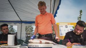 Ralf Snellman väger en av fisketävlingens foreller på en våg.