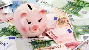 En spargris står på ett hav av pengar.