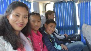 En kvinna och hennes barn sitter på en buss.