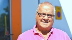 Närbild, porträtt, av Lars Nyberg från SDP. Bär glasögon och iklädd i rosa t-skjorta.