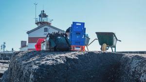 Kottikärryt, muovilaatikoita täynnä tavaraa ja iso reppu kalliolla. Taustalla punavalkoraidallinen majakka.