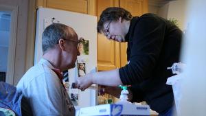 En man sitter hemma i sitt kök och får medicin genom en kateter av en sjukskötare.