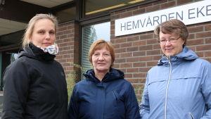 Tre kvinnor står på rad framför en röd tegelbyggnad.