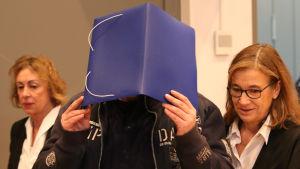 En svartklädd man täcker sitt ansikte med en pärm.