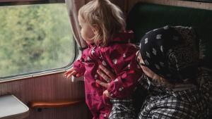 Pieni lapsi pinkkiin haalariin pukeutuneena isoäitinsä sylissä, katsoo junan ikkunasta ulos.