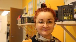 En kvinna i 30-årsåldern med rött hår och glasögon står bredvid en gul vägg i en skolkorridor.