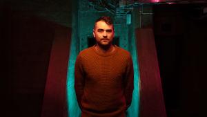 Johannes Björkqvist står i ett mörkt rum.  Ljuset som faller på honom skifar från magenta till gult.