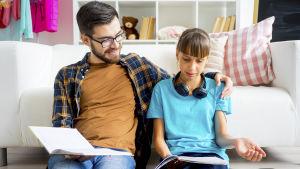 en pappa hjälper sin tonårsdotter med läxor.