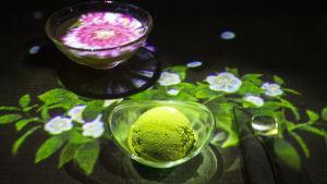 Lasisessa teekupissa teehen puhkeaa kukkia ja kulhossa on vihreää jäätelöä