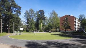 En park med en gräsplätt på mitten. På höger sida syns ett rött tegelhus,