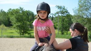 Sexåriga Ellen Lankinen uppe i sadeln medan mamma Paula hjälper till.