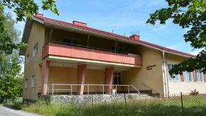 Norrskata skola är ett gulrappat hus i 1-2 våningar. Gräset är övervuxet.