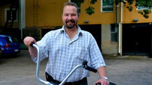En man i rutig skjorta står vid en cykel och ler.