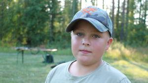 En pojke med keps på huvudet står framför en skogsdunge.