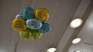 """Folieballonger fyllda med helium i en hopsamlad """"bukett"""" svävar mot ett vitt trätak.  Ballongerna är i gult, turkos och grönt. De har siffran 30 i mitten."""