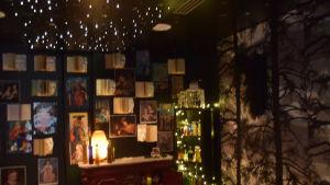 Ett mörkt rum med böcker och affischer på väggarna. Stämningsbelysning i form av ljusgirlanger. Bibliotek, sagorum.