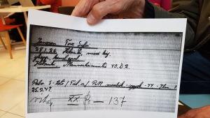 En hand håller upp ett papper med en gammal namnteckning.