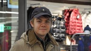 Paavo i närbild, står utanför en butik som säljer vinterjackor.