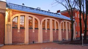 Gymnastiksalen utifrån, den har tegelväggar och valv kring fönstren.