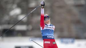 Therese Johaug sträcker armen i luften