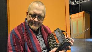 Johan Fröberg, en man med glasögon och rödblårandig morgonrock, lyssnar på en gammal radio han har i famnen.